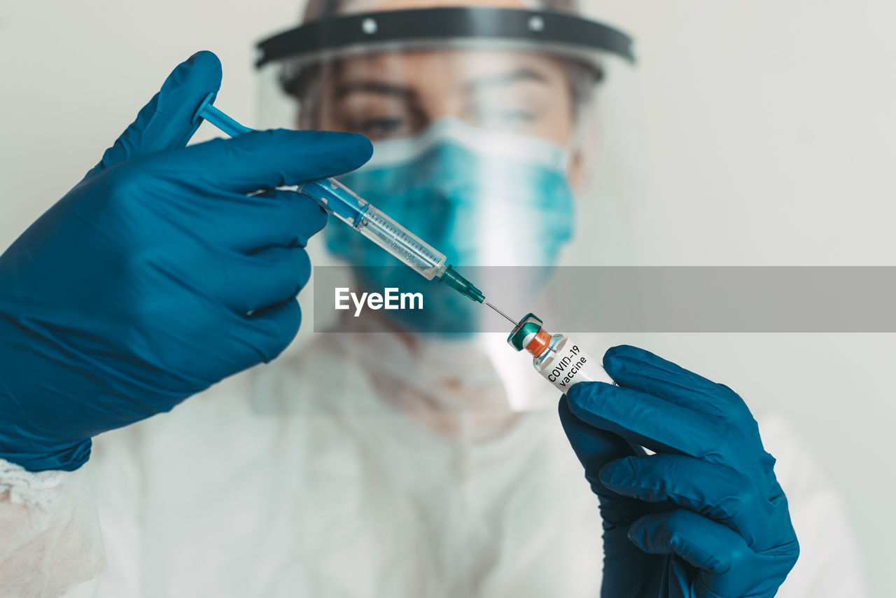 Close-up of doctor injecting syringe in vial at hospital