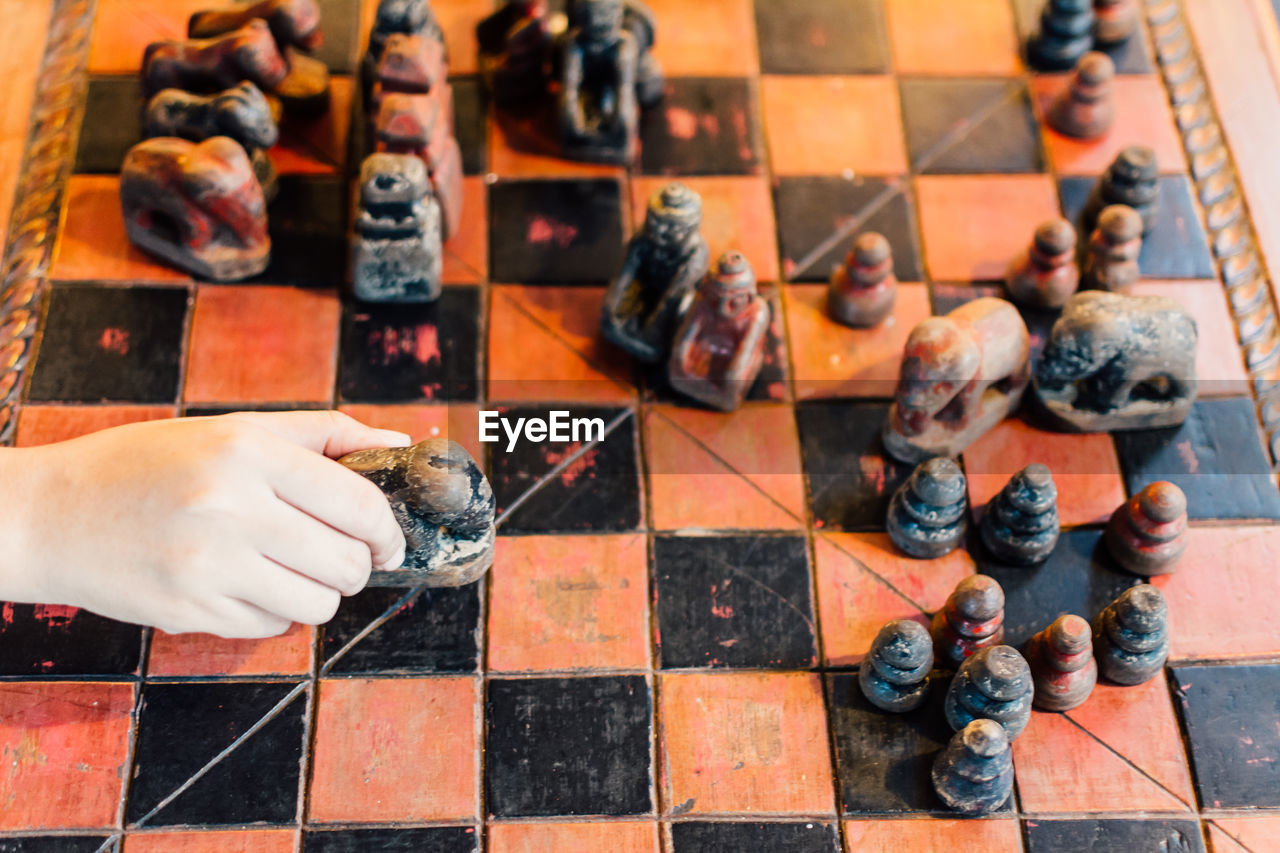 chess, chess piece, chess board, leisure games, board game, checked pattern, real people, strategy, high angle view, playing, leisure activity, indoors, day, human body part, one person, game, human hand, pawn - chess piece, knight - chess piece, competition, close-up, queen - chess piece