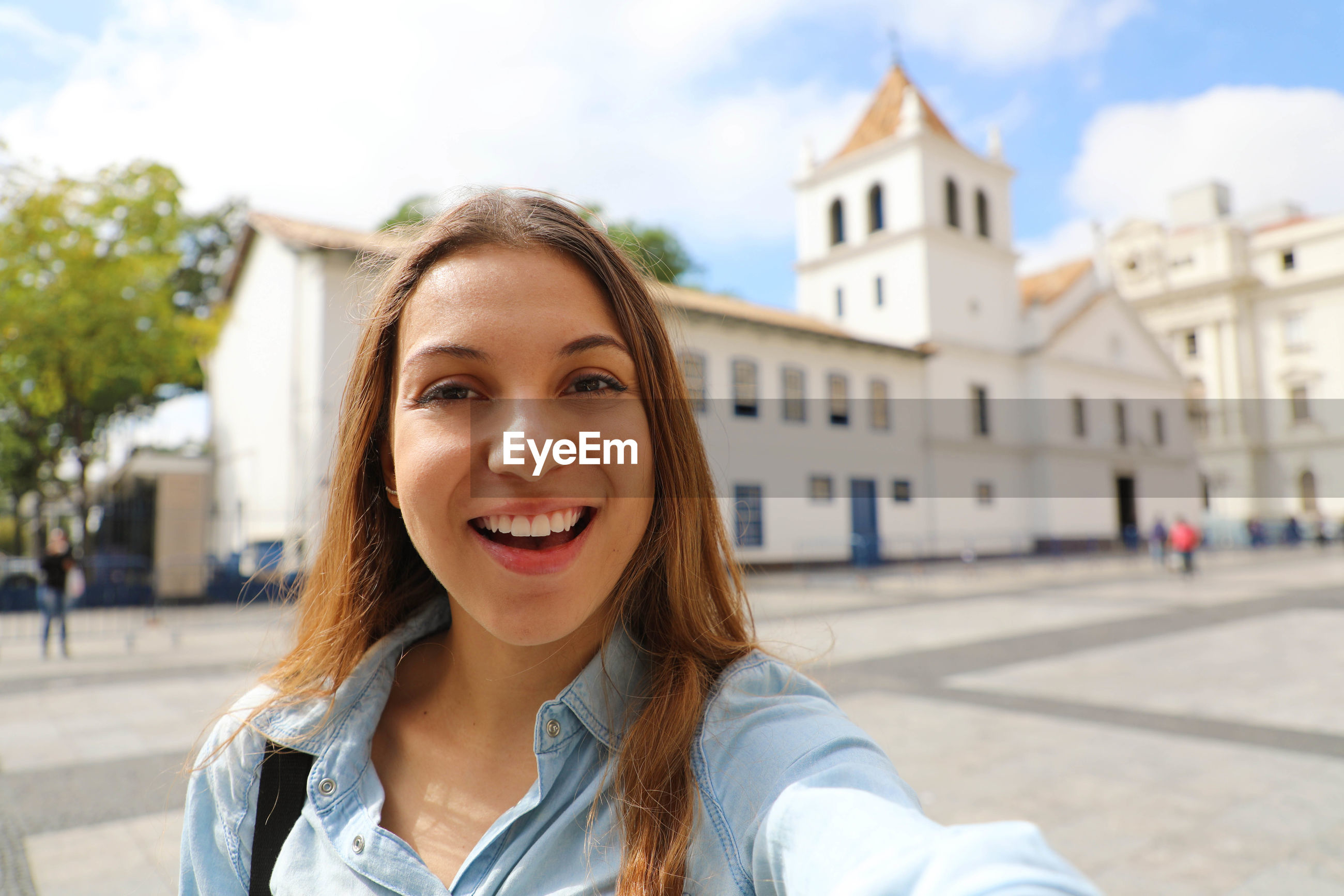 Portrait of smiling young woman against buildings