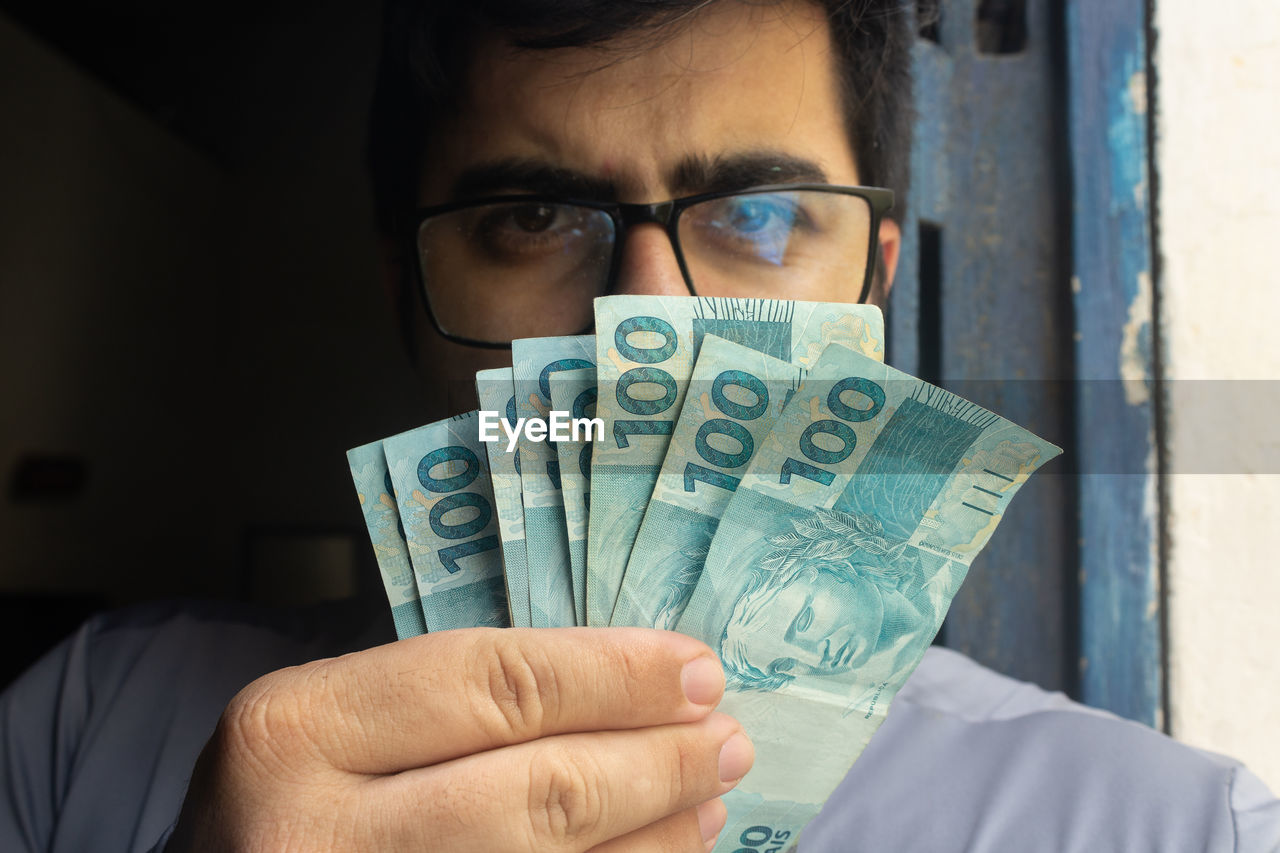 Portrait of man holding banknotes at home