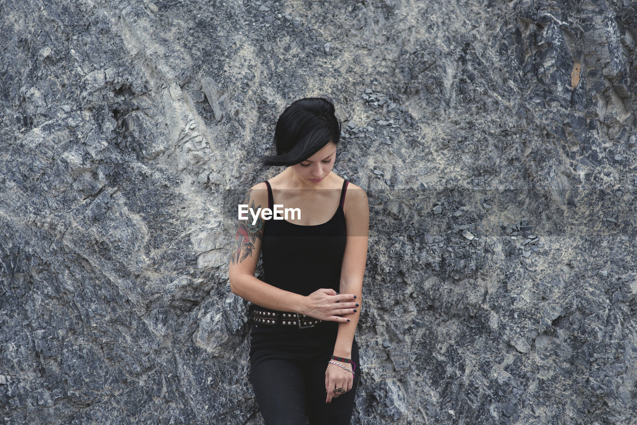 Sad Woman Standing Against Rock Formation