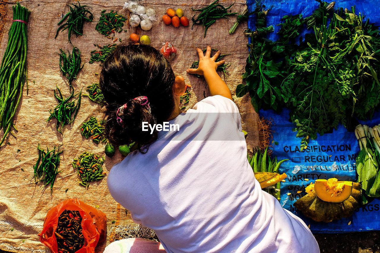Rear View Of Vendor Arranging Vegetables On Plastic Sheet In Market