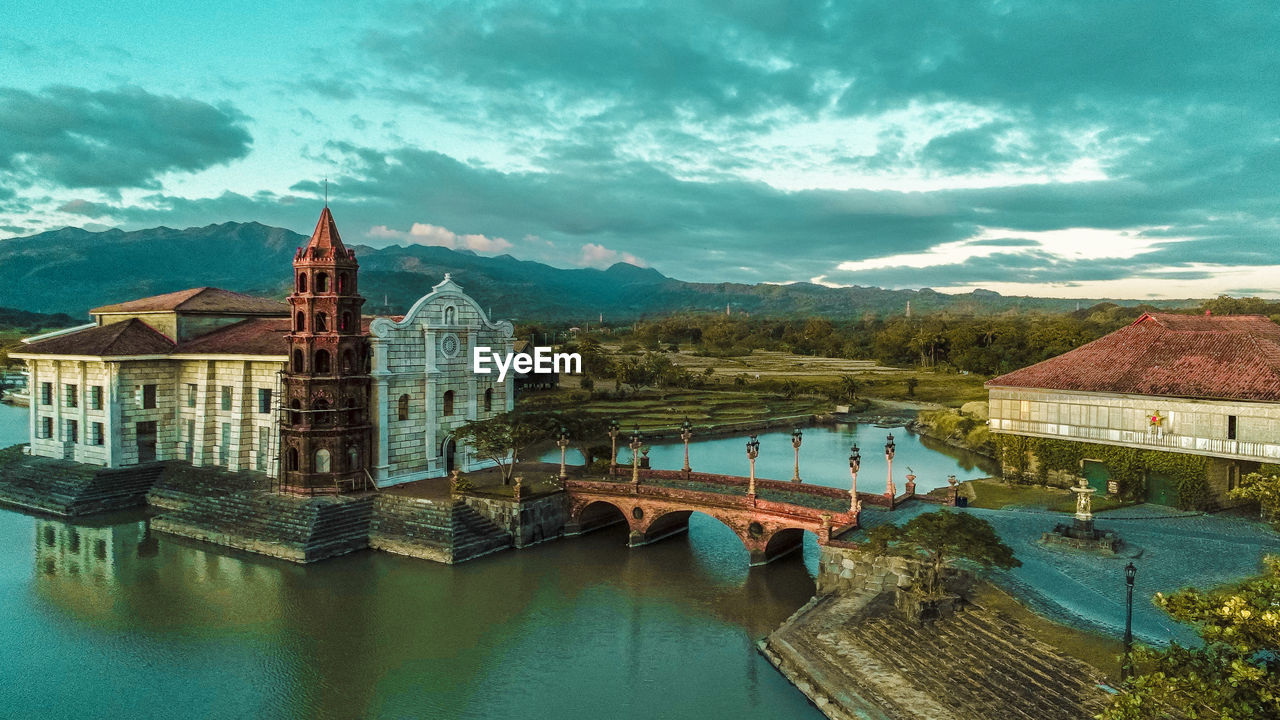architecture, built structure, building exterior, building, mountain, sky, water, cloud - sky, nature, the past, no people, travel destinations, history, city, mountain range, residential district, river, day, religion, outdoors
