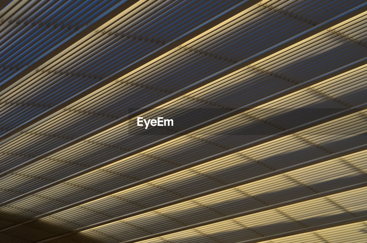 pattern, full frame, backgrounds, no people, textured, indoors, repetition, metal, day, close-up, striped, sunlight, gold colored, wood - material, blinds, yellow, high angle view, wall - building feature, abstract, silver colored