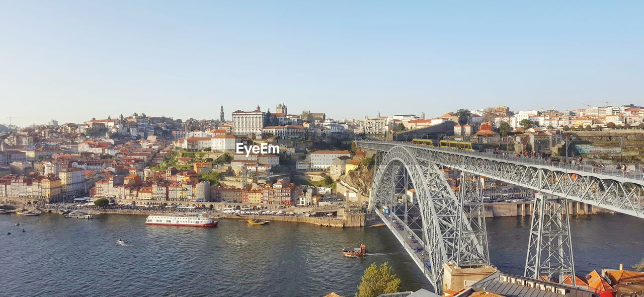 architecture, built structure, water, city, bridge, building exterior, transportation, connection, river, sky, bridge - man made structure, cityscape, nature, clear sky, day, building, copy space, waterfront, residential district, no people, outdoors, arch bridge