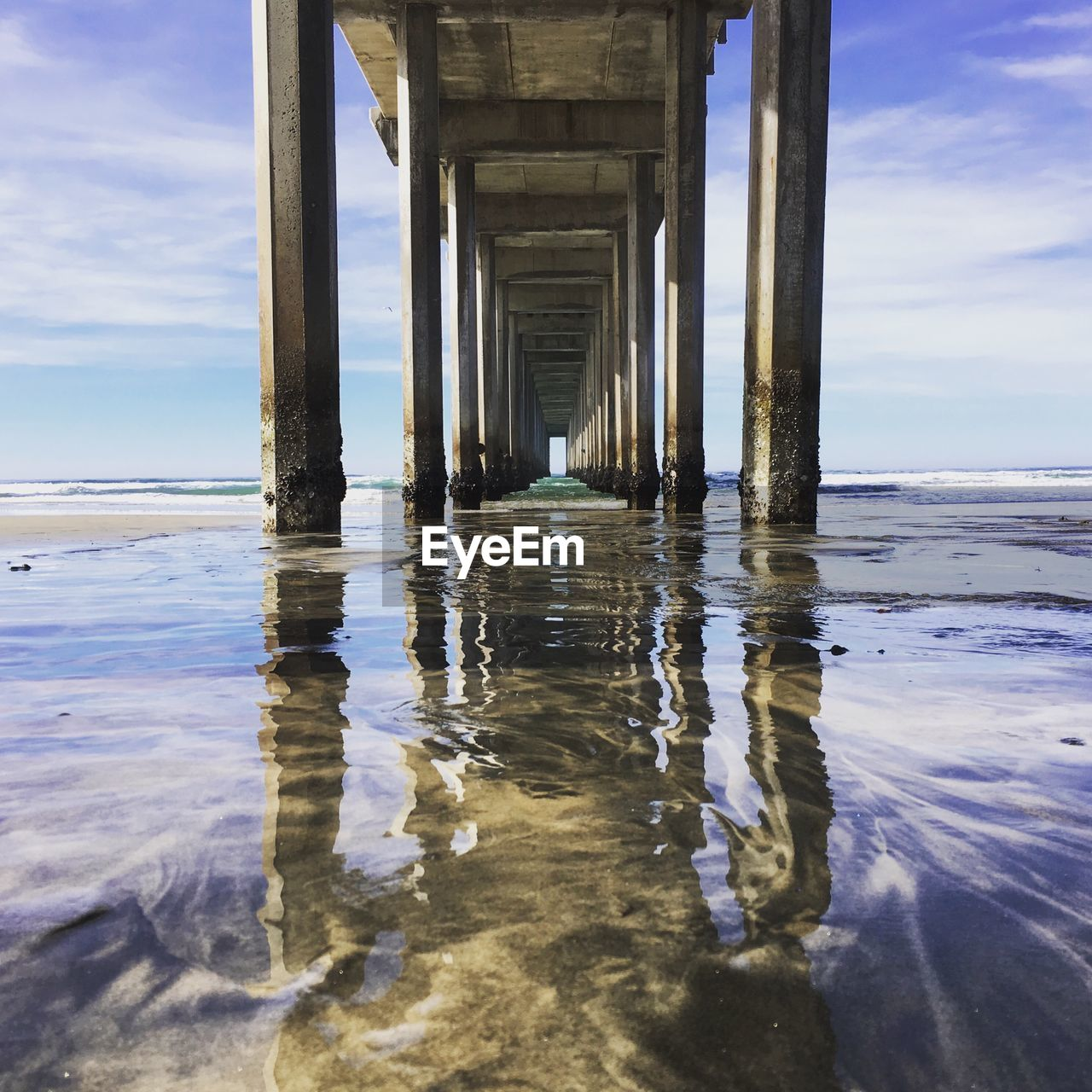 water, sea, underneath, nature, tranquility, day, pier, cloud - sky, sky, outdoors, below, tranquil scene, scenics, waterfront, architectural column, no people, beauty in nature, horizon over water, architecture, beach, built structure, under