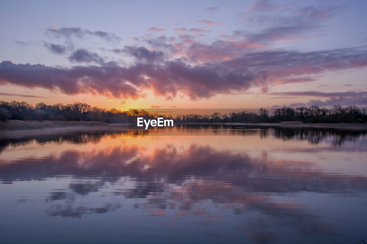 sky, reflection, sunset, water, tranquility, tranquil scene, beauty in nature, scenics - nature, cloud - sky, waterfront, lake, nature, no people, orange color, idyllic, symmetry, non-urban scene, tree, outdoors, reflection lake