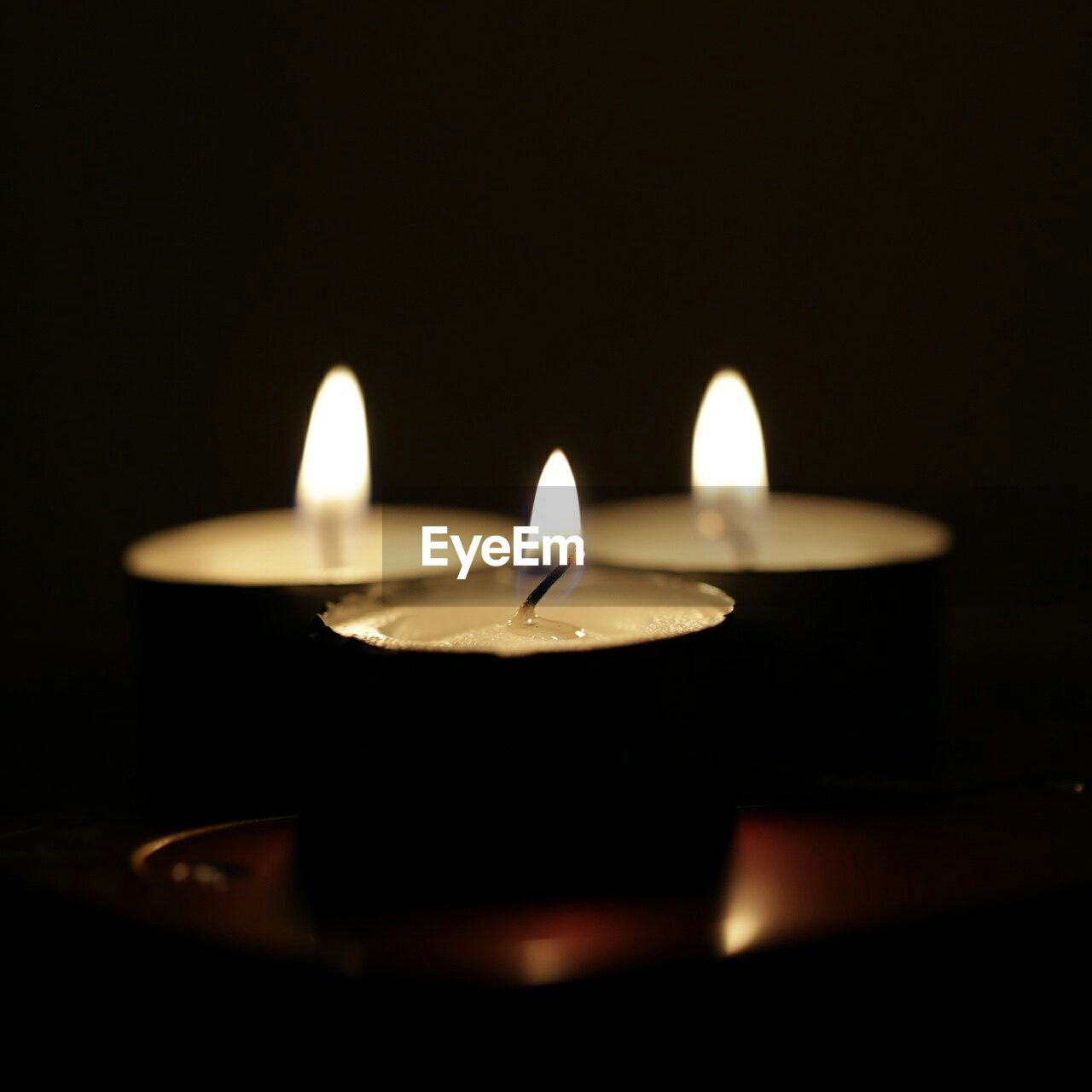 Lit Tealight Candles In Dark Room
