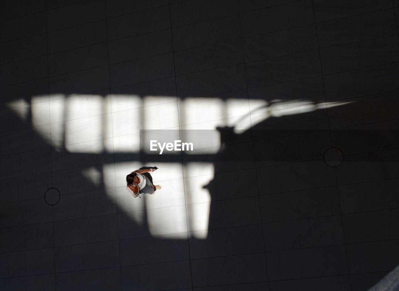 High angle view of woman on tiled floor