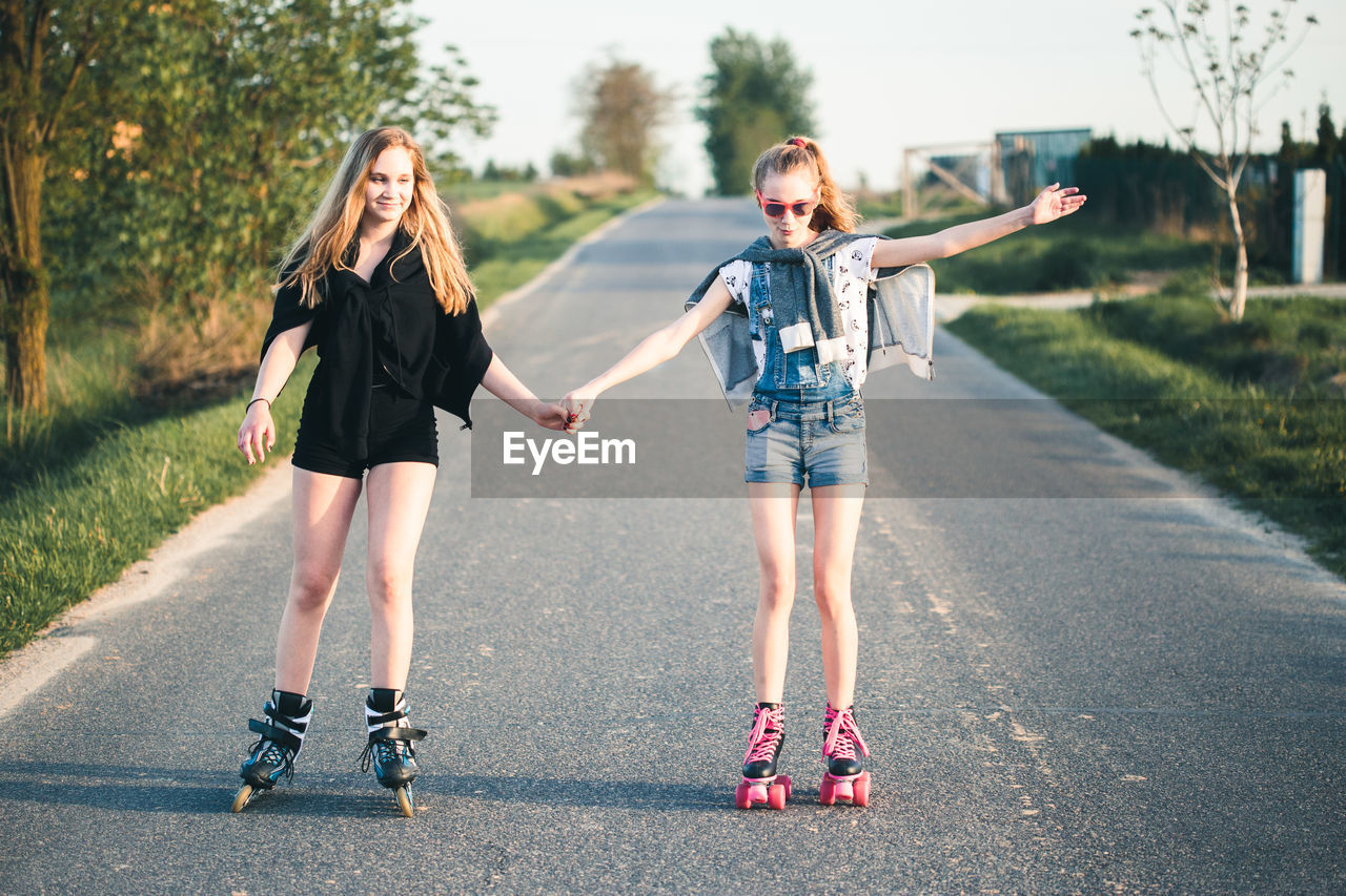 togetherness, full length, real people, child, two people, road, childhood, transportation, girls, women, lifestyles, females, city, roller skate, casual clothing, day, leisure activity, people, bonding, outdoors, positive emotion, sister
