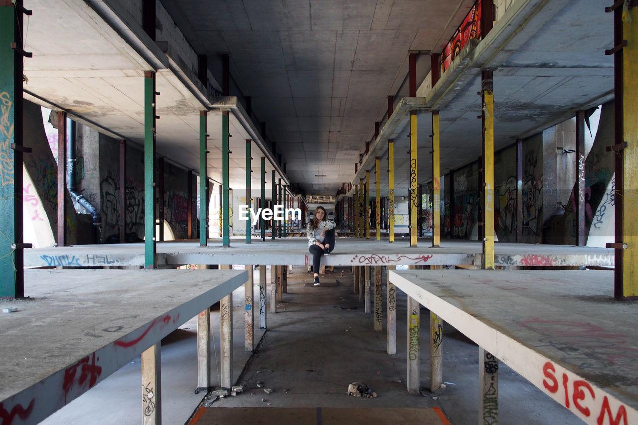 MAN WALKING ON BRIDGE IN BUILDING