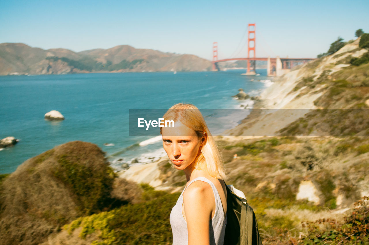 Portrait Of Woman Standing At Sea Shore By Golden Gate Bridge Against Clear Sky
