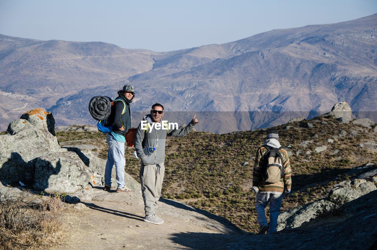 People standing on rocks against mountain range