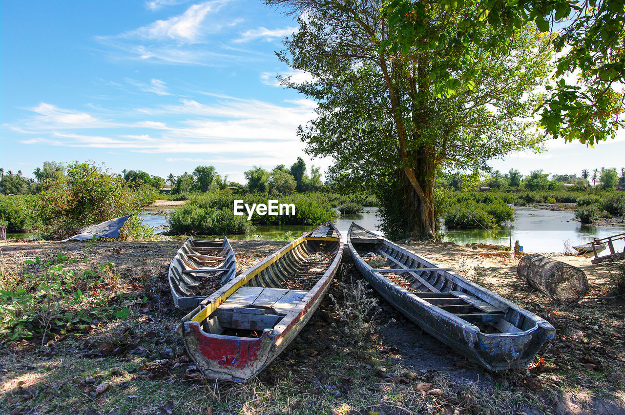 Old Boats On Field By River Against Tree