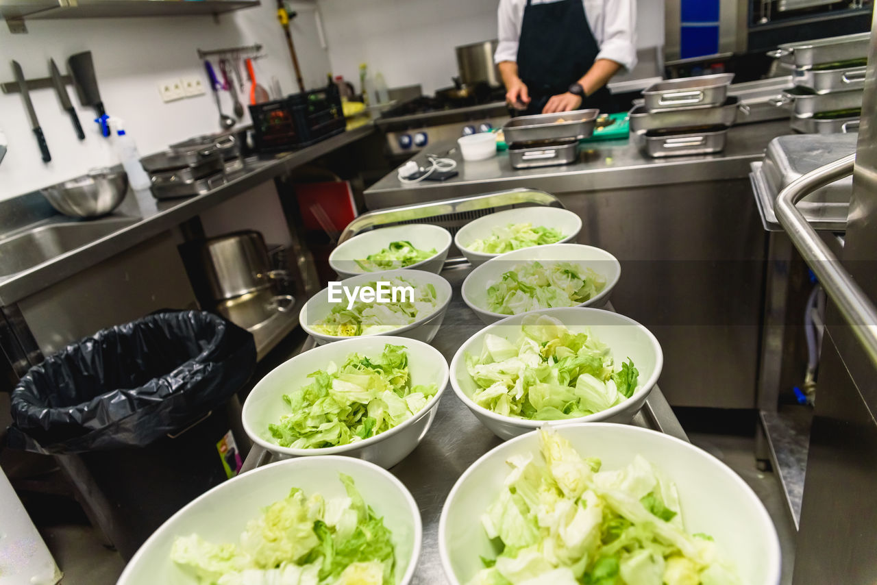 food and drink, food, vegetable, healthy eating, indoors, preparing food, freshness, wellbeing, kitchen, bowl, preparation, table, real people, salad, domestic room, commercial kitchen, midsection, business, one person, kitchen utensil, chef