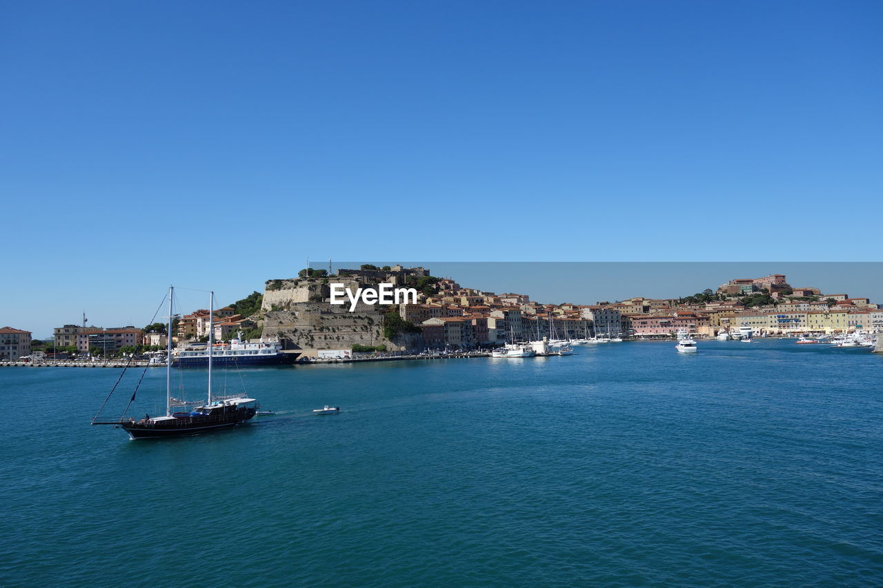 View Of Town In Sea Against Blue Sky