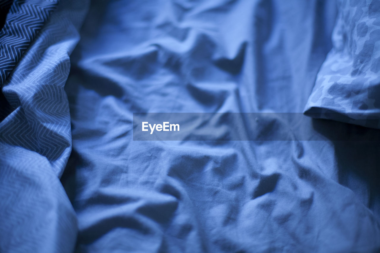 textile, crumpled, no people, bed, full frame, close-up, indoors, linen, backgrounds, furniture, bedroom, sheet, still life, wrinkled, high angle view, blue, selective focus, pattern, textured, messy, duvet
