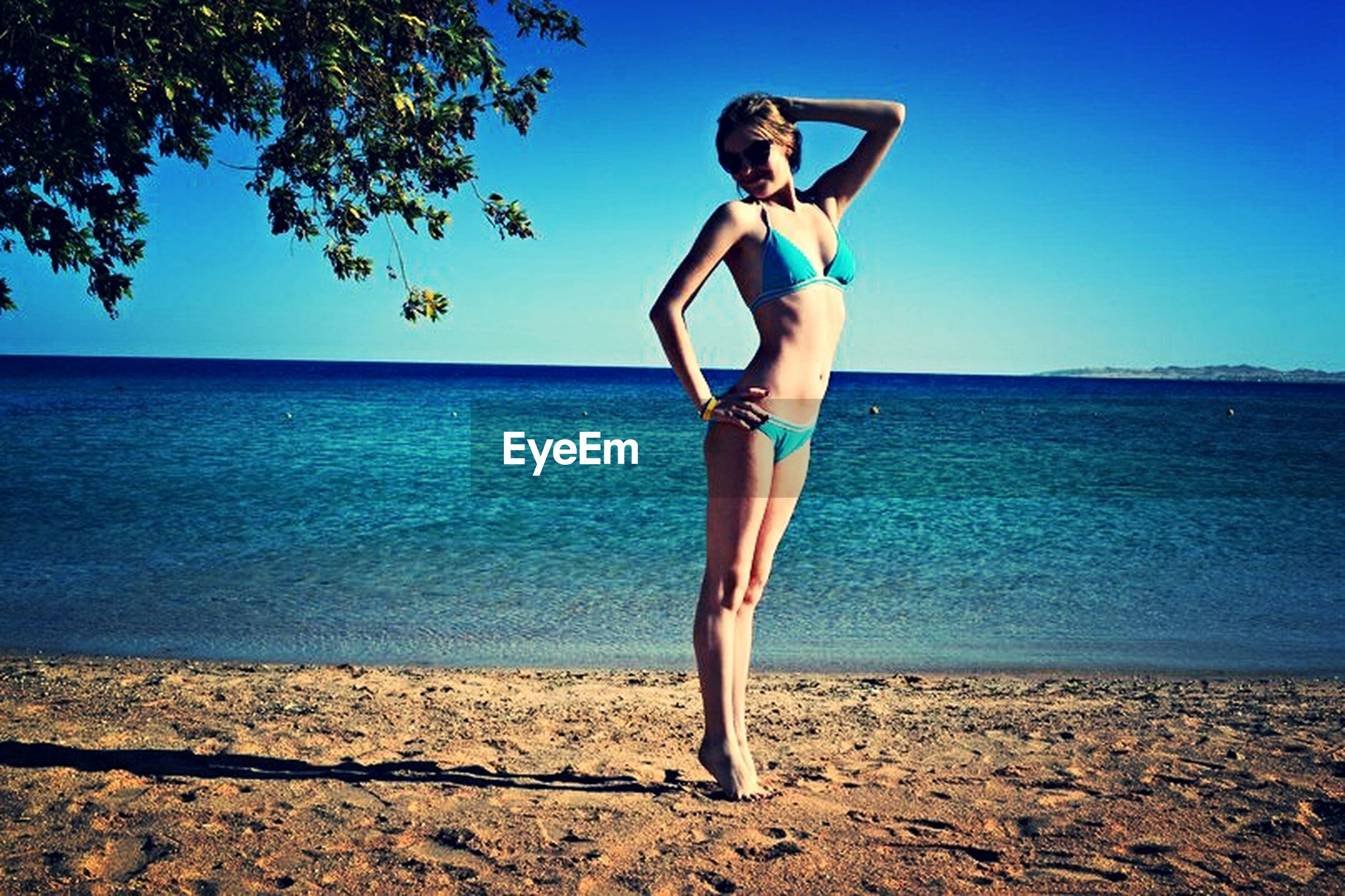 young adult, sea, person, full length, beach, water, lifestyles, leisure activity, shore, horizon over water, sunglasses, casual clothing, young women, portrait, vacations, looking at camera, front view, standing