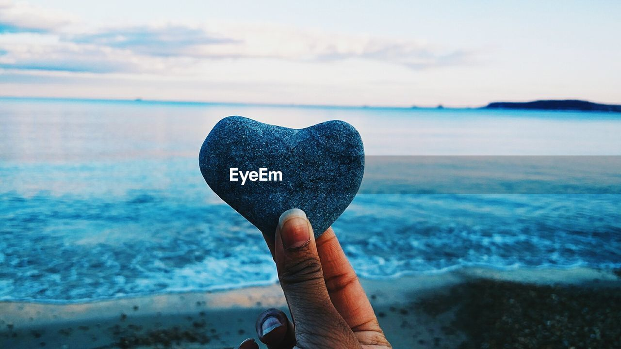 Cropped image of person holding heart shape stone at beach