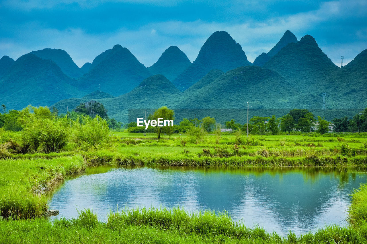 mountain, beauty in nature, nature, scenics, mountain range, tranquil scene, green color, reflection, tranquility, outdoors, water, lake, day, no people, landscape, sky, tree, grass
