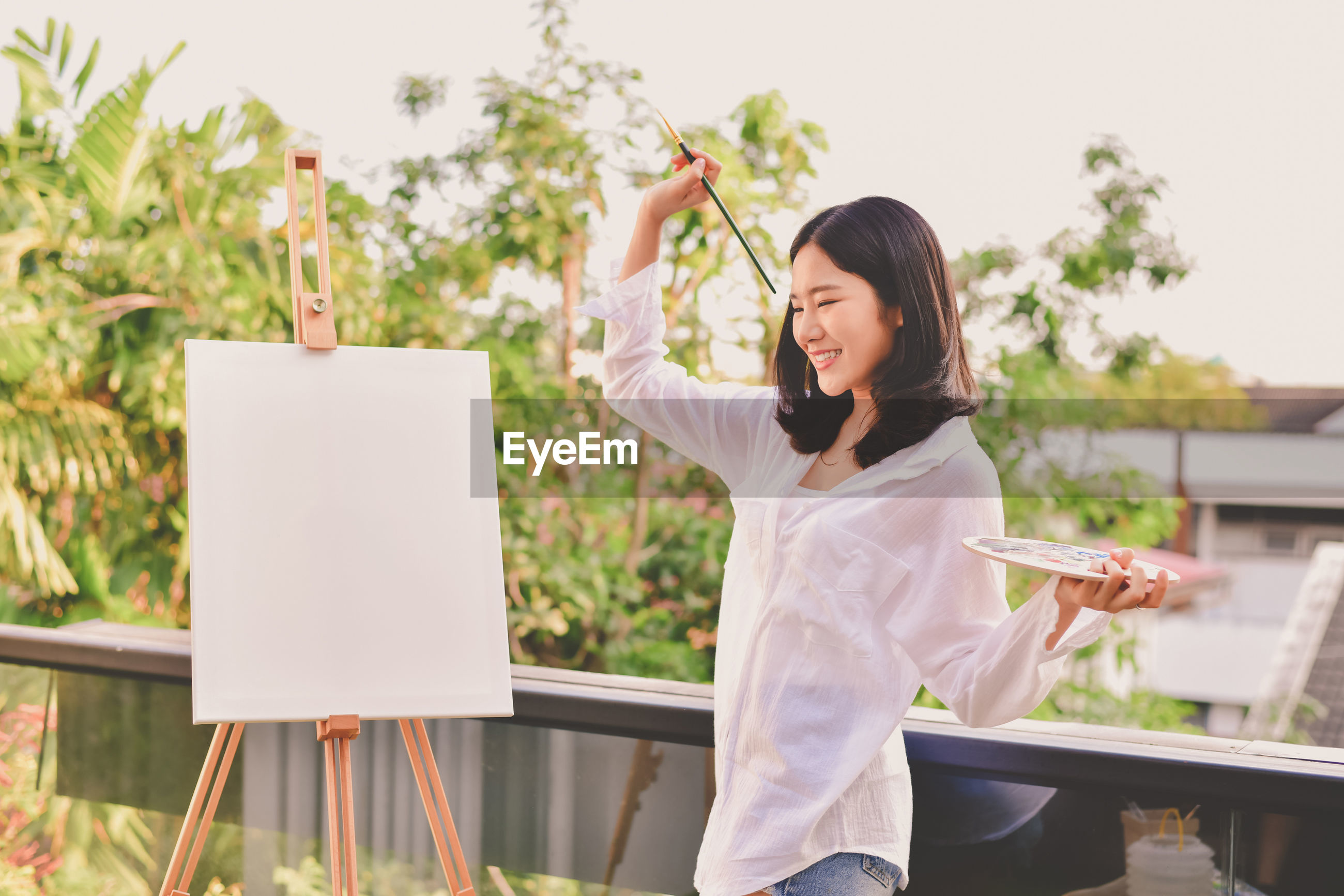 Smiling woman standing by canvas against sky