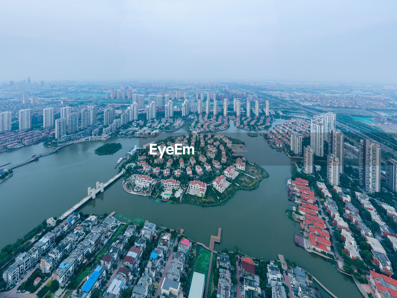 HIGH ANGLE VIEW OF BUILDINGS BY RIVER AGAINST SKY