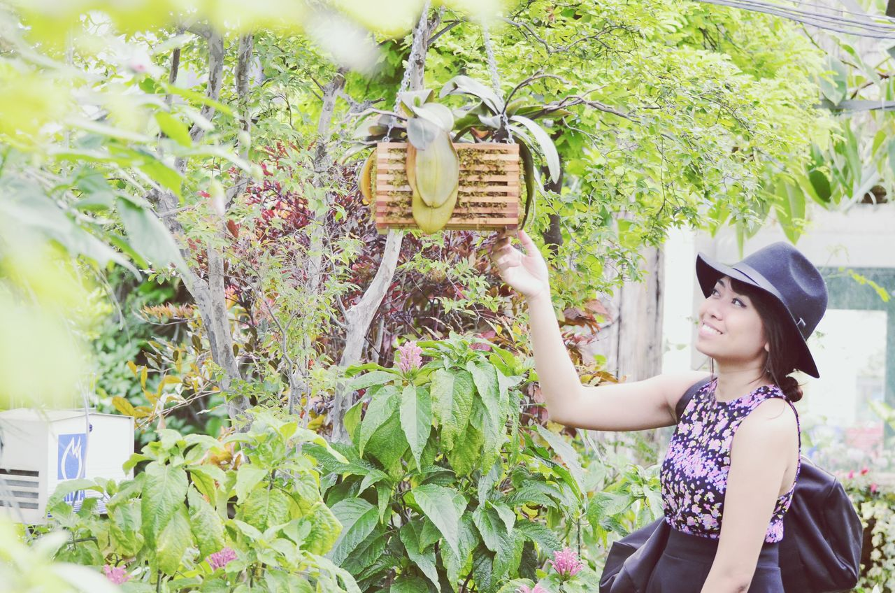 Happy Woman Touching Beehive Hanging On Tree