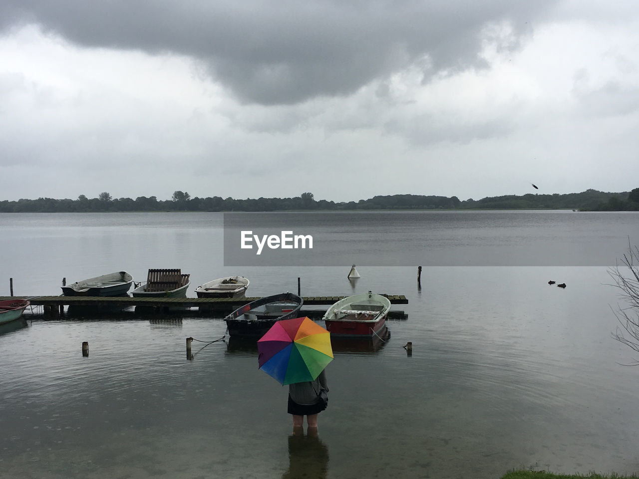 water, sky, cloud - sky, transportation, nautical vessel, mode of transportation, day, nature, lake, beauty in nature, reflection, scenics - nature, outdoors, overcast, protection, waterfront, tranquility, tranquil scene, rain