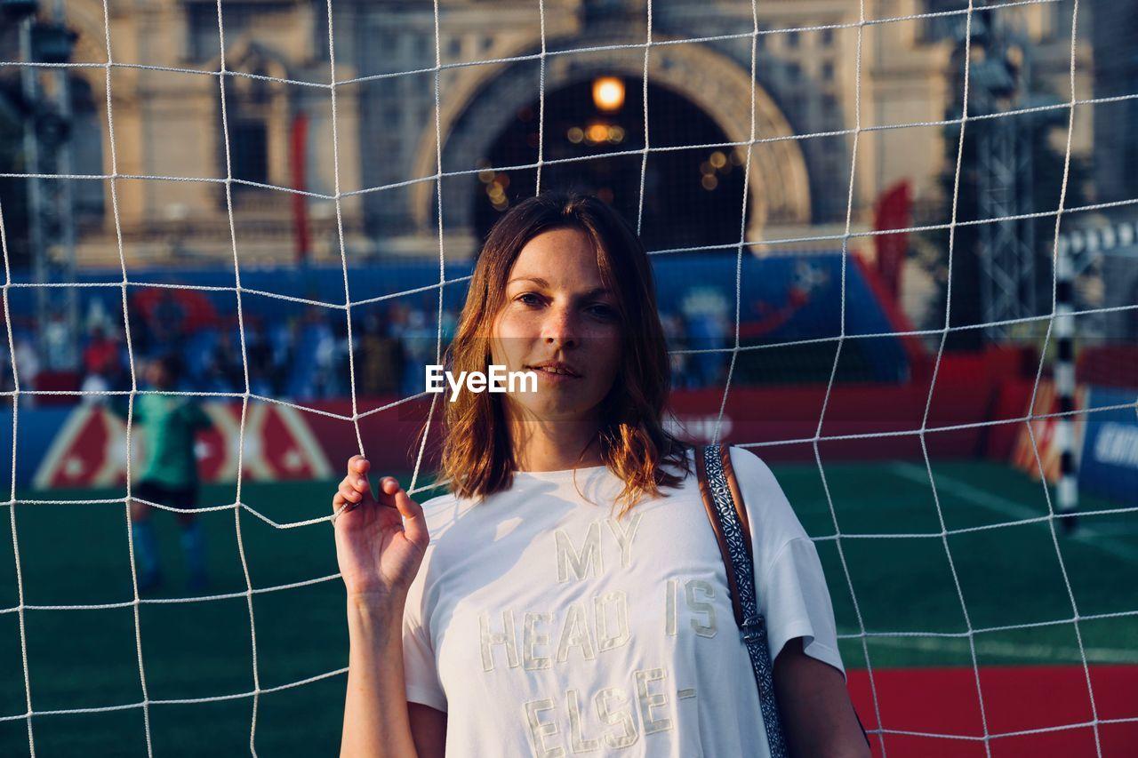 Portrait Of Woman Standing By Net