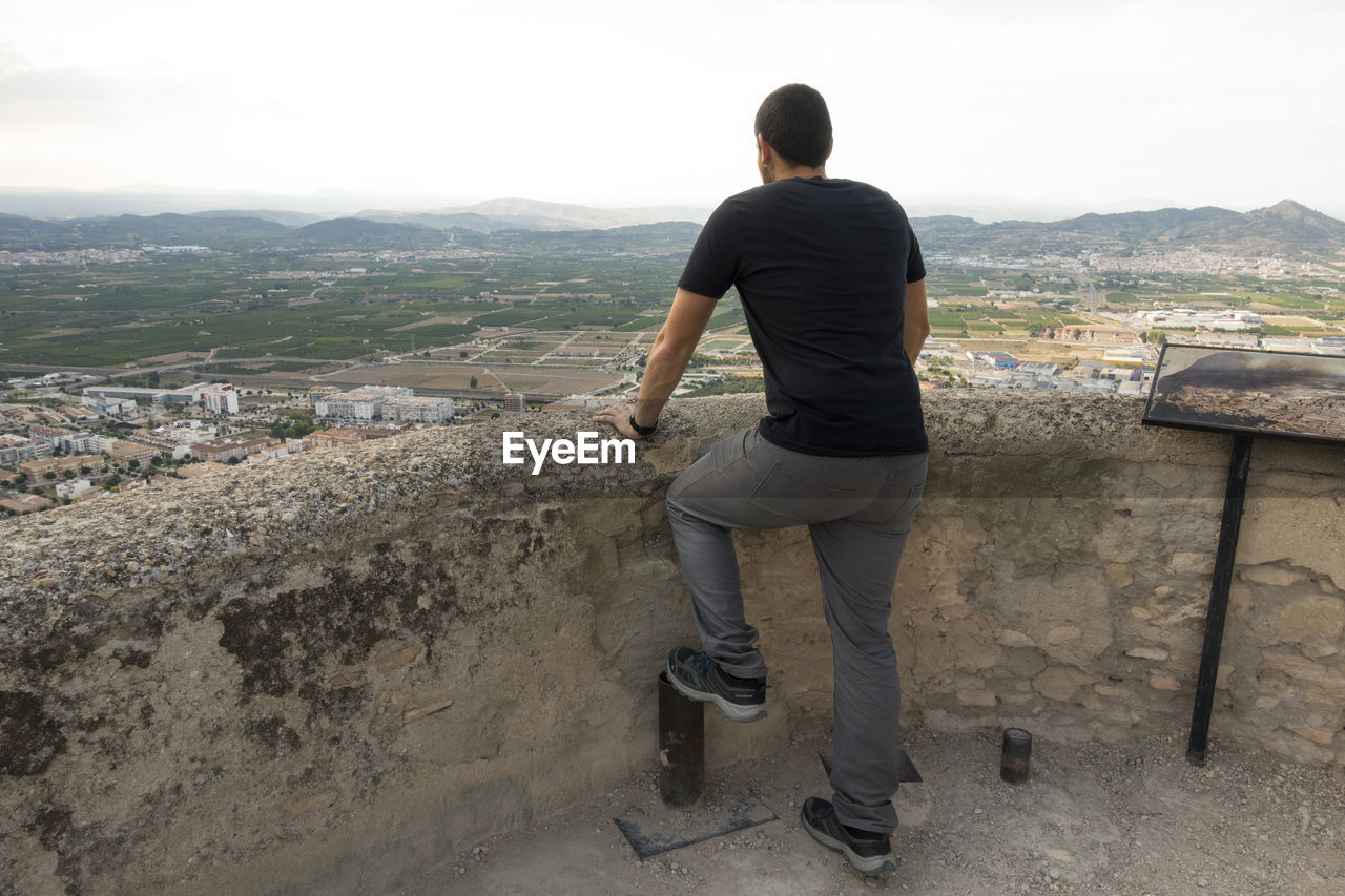 Rear View Of Man Looking At Landscape Against Sky