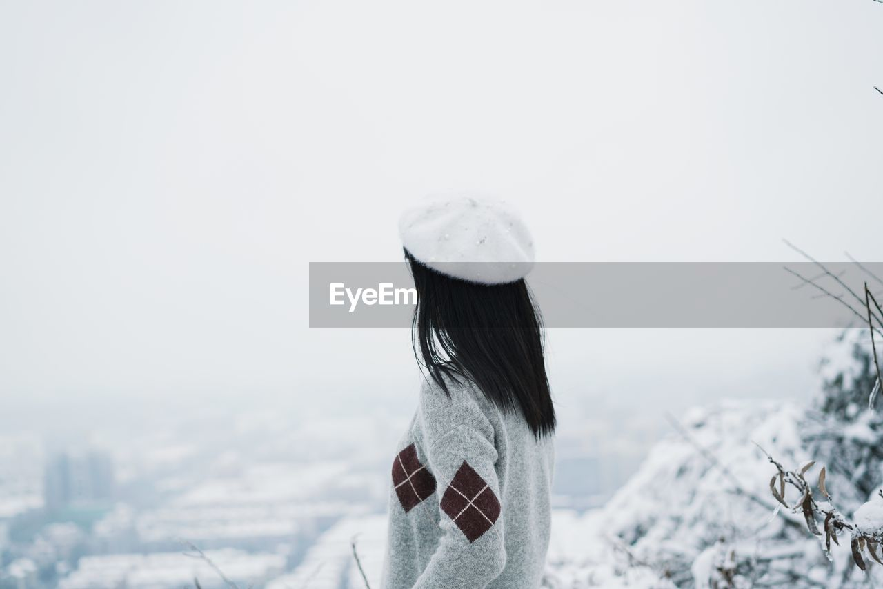 Side View Of Woman Against Clear Sky During Winter
