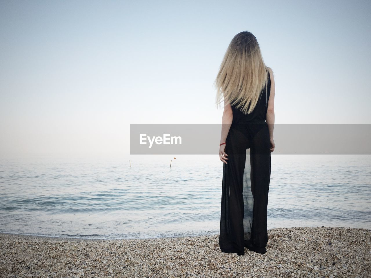 Rear view of woman standing on the shore