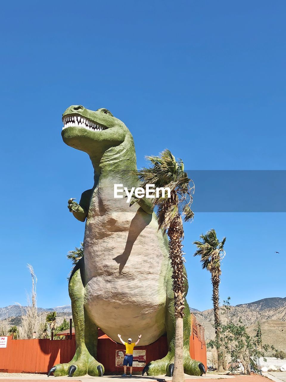 statue, sculpture, day, animal representation, blue, reptile, outdoors, no people, tree, animal themes, sunlight, nature, clear sky, low angle view, animals in the wild, iguana, dragon, sky