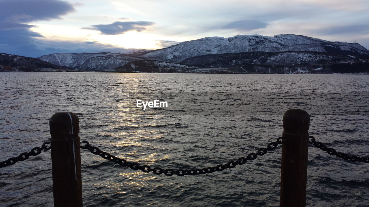 Scenic View Of Sea By Snowcapped Mountains During Sunset