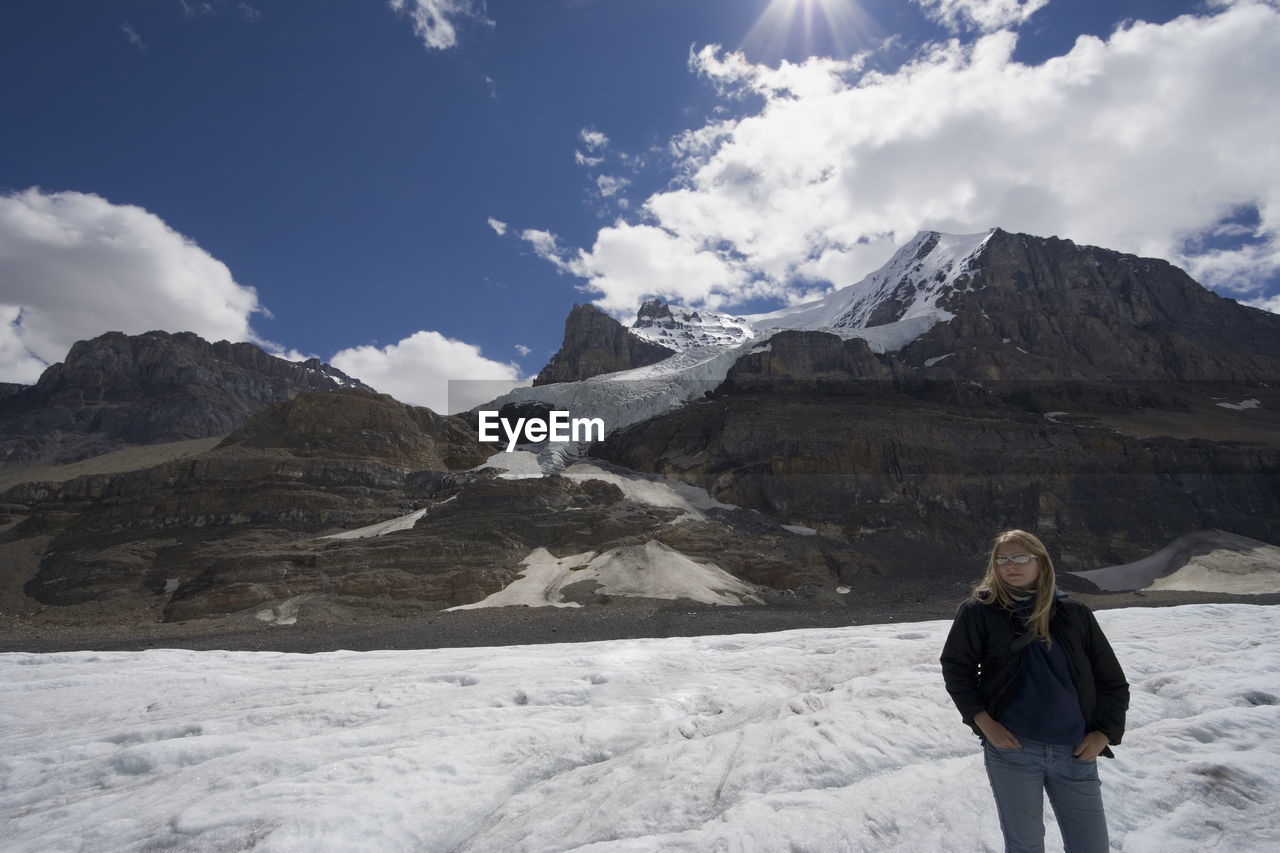 Full Length Of Woman On Snowcapped Mountains Against Sky