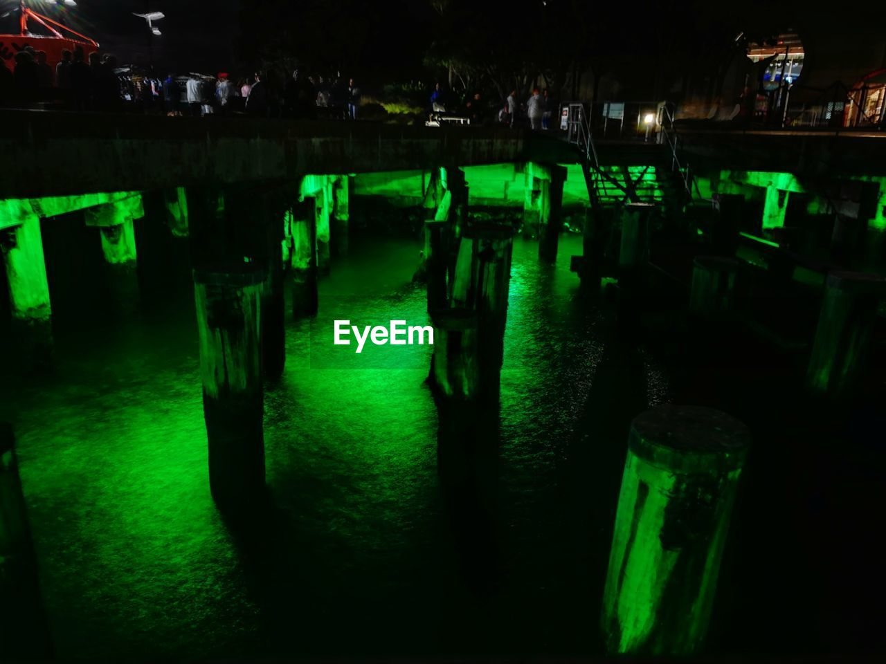 night, green color, water, illuminated, reflection, real people, in a row, group, architecture, table, standing, lake, outdoors, leisure activity, nature, chair, swimming pool, bar counter, nightlife