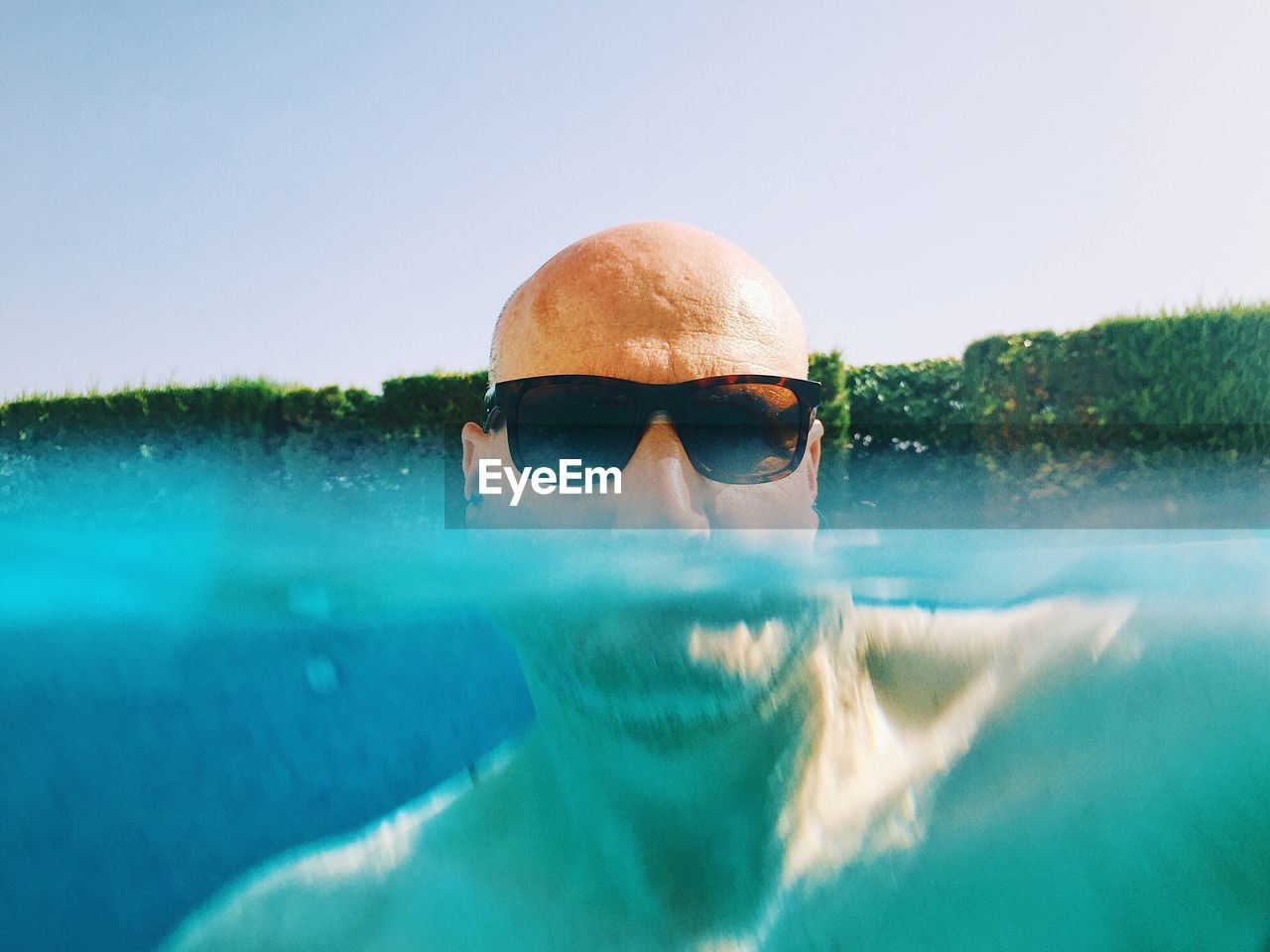 Portrait Of Bald Man Wearing Sunglasses While Swimming In Pool Against Clear Sky