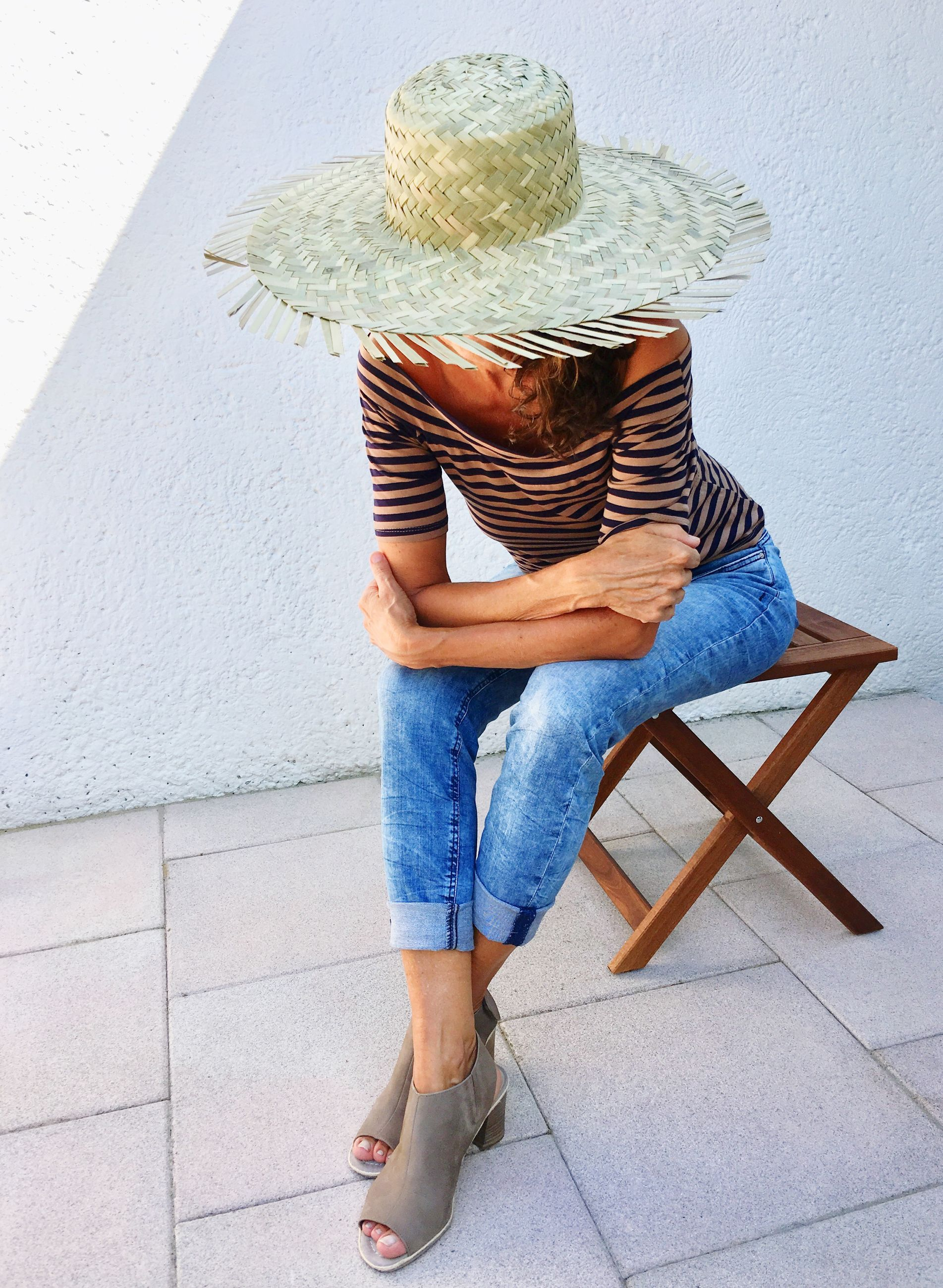Woman wearing hat while sitting against wall