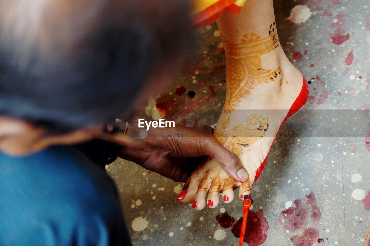 Close-up of woman applying red nail polish to bride