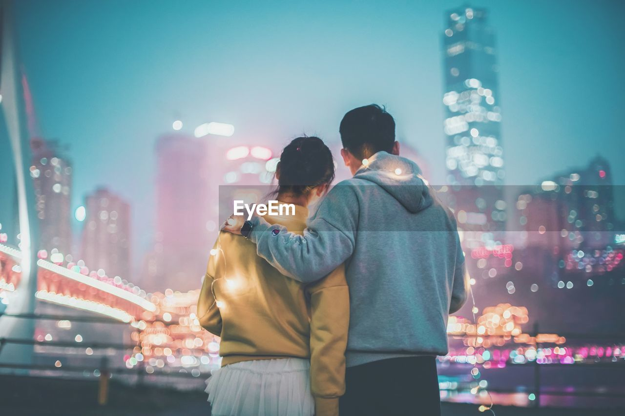 two people, togetherness, love, night, illuminated, bonding, architecture, men, building exterior, positive emotion, built structure, city, adult, emotion, couple - relationship, women, real people, three quarter length, city life, standing, skyscraper, office building exterior, arm around, outdoors, cityscape
