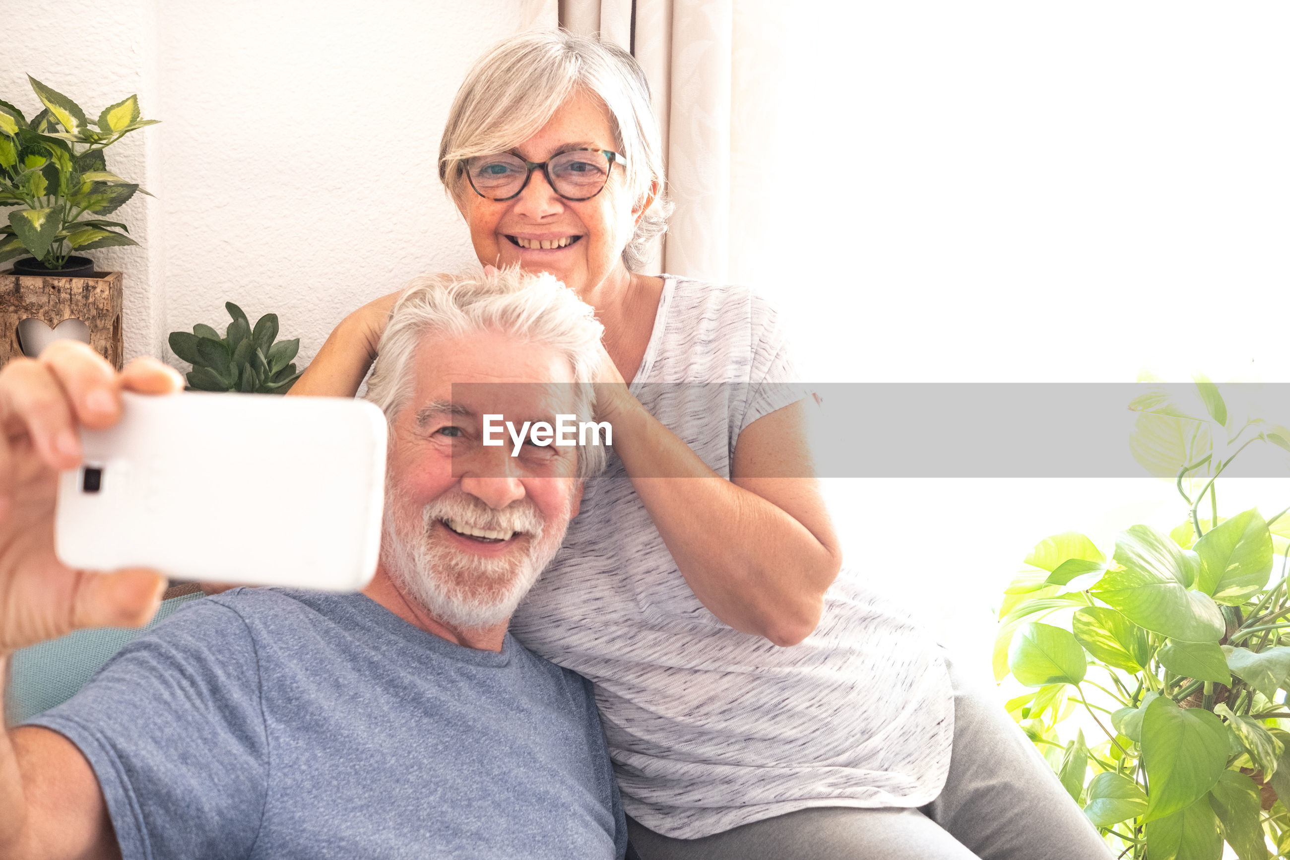 Smiling senior couple taking selfie on mobile phone at home