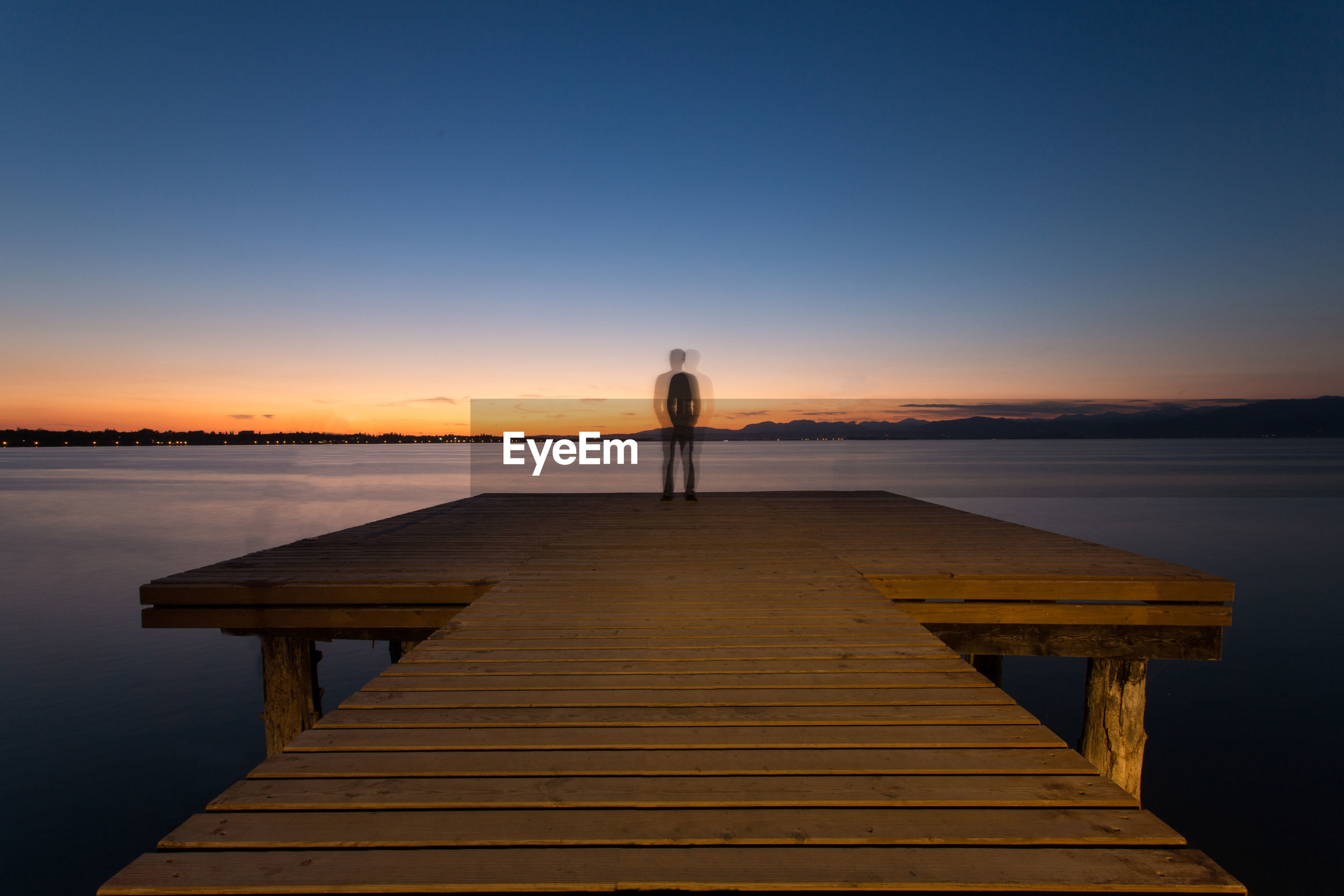Man on pier against romantic sky at sunset