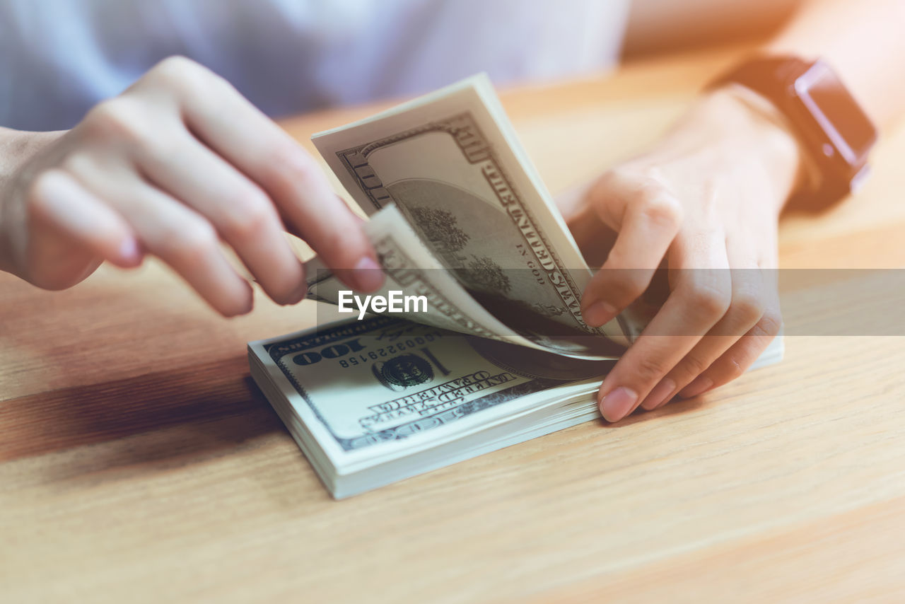 Midsection Of Woman Counting Paper Currencies At Table