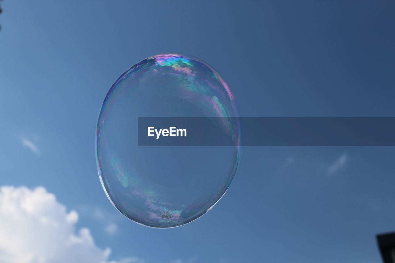 bubble, fragility, sky, nature, mid-air, sphere, transparent, vulnerability, no people, soap sud, day, low angle view, focus on foreground, shape, close-up, flying, reflection, outdoors, geometric shape, beauty in nature, lightweight