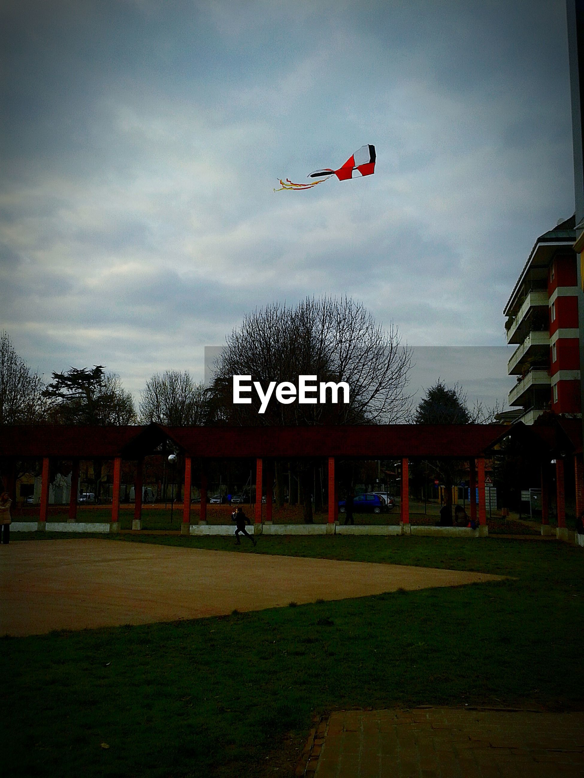 Low angle view of kite flying by building against cloudy sky
