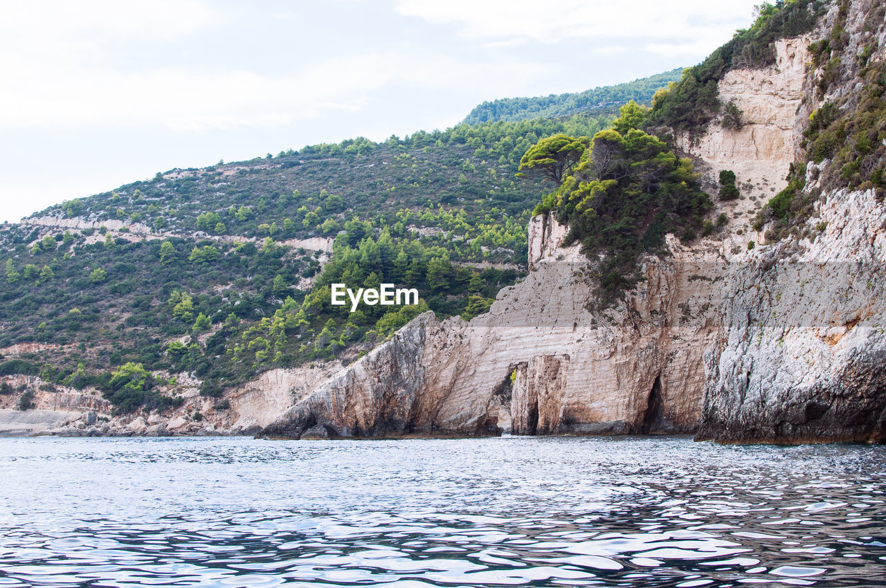 Scenic view of mountain by sea against sky