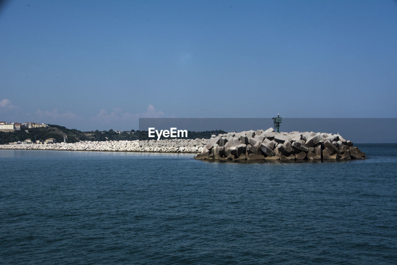 water, waterfront, sea, sky, scenics - nature, beauty in nature, tranquil scene, rock, day, tranquility, rock - object, nature, copy space, blue, solid, no people, non-urban scene, idyllic, rippled, outdoors, groyne