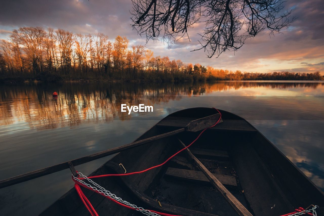 Boat and oar in lake against sky