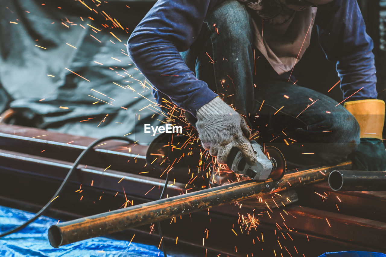 real people, one person, occupation, men, working, metal, holding, skill, industry, midsection, indoors, sparks, front view, heat - temperature, nature, day, human hand, focus on foreground, welding, metal industry, effort