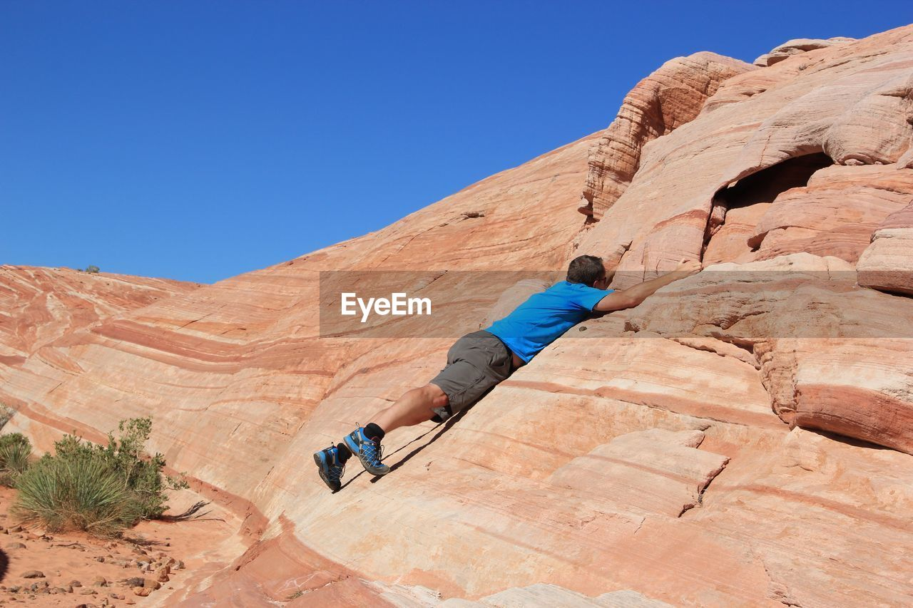 Man Clambering On Rock Without Equipment